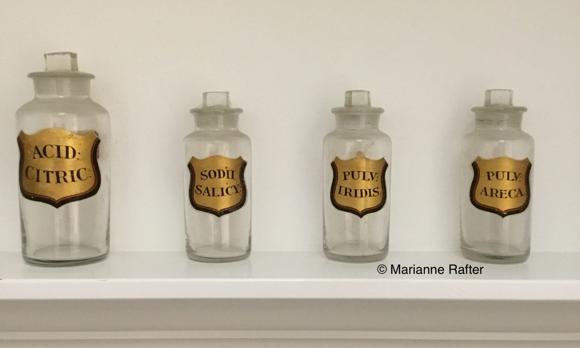 Old glass pharmacy bottles with gold labels